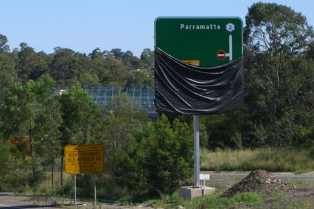 closeup of advanced direction sign for Westlink M7, partially covered up, showing