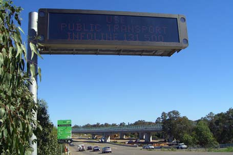 variable message sign displaying 'Use Public Transport/Infoline 131500' with the WestlinkM7 in the background